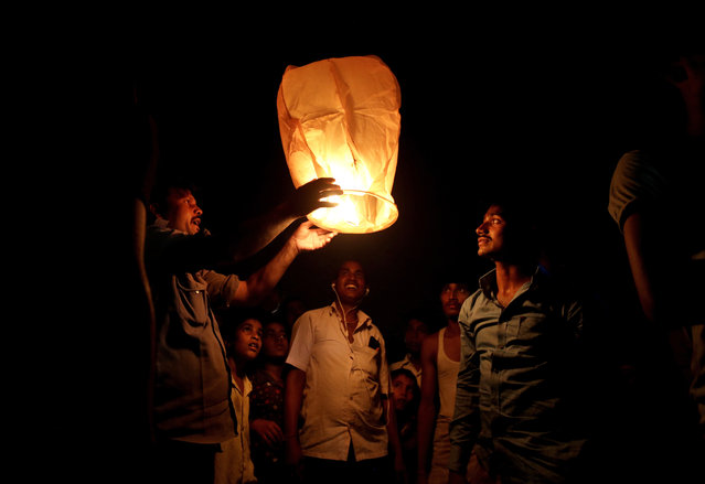 Indians light a sky lantern to celebrate Diwali festival in New Delhi, India, Thursday, October 19, 2017. Diwali, a major Hindu festival for more than a billion Indians, includes lighting oil lamps or candles to symbolize a victory of knowledge over ignorance, light over darkness and good over evil. (Photo by Altaf Qadri/AP Photo)