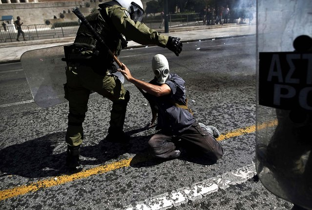 A demonstrator scuffles with a police officer during clashes in Athens, Greece, on September 26, 2012. Widespread protests erupted across Greece after trade unions called a nationwide strike to contest new salary and pension cuts being discussed by the government. (Photo by Angelos Tzortzinis/The New York Times)