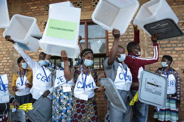 "Electoral officials hold up ballot boxes to show they are empty before voters cast their votes in the presidential election, in Giheta, Gitega province, Burundi Wednesday, May 20, 2020. A crucial election has begun in the East African nation of Burundi, where President Pierre Nkurunziza is stepping aside after a divisive 15-year rule but will remain ""paramount leader"" in the country that continues to reject outside scrutiny. (Photo by Berthier Mugiraneza/AP Photo)"