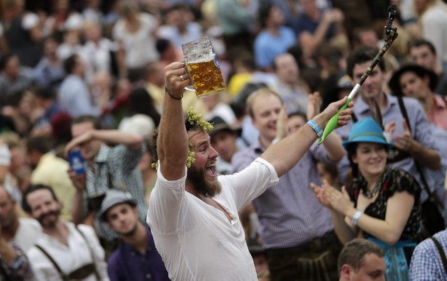 A man celebrates the opening of the 181st Oktoberfest beer festival in Munich, southern Germany, Saturday, September 20, 2014. (Photo by Matthias Schrader/AP Photo)