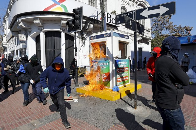 Masked and hooded demonstrators run away after setting a security guard post on fire during a protest marking the country's 1973 military coup, in Santiago, Chile September 13, 2015. Chile marks the start of the coup d'etat that ushered in a 17-year dictatorship under General Augusto Pinochet on September 11. (Photo by Ivan Alvarado/Reuters)