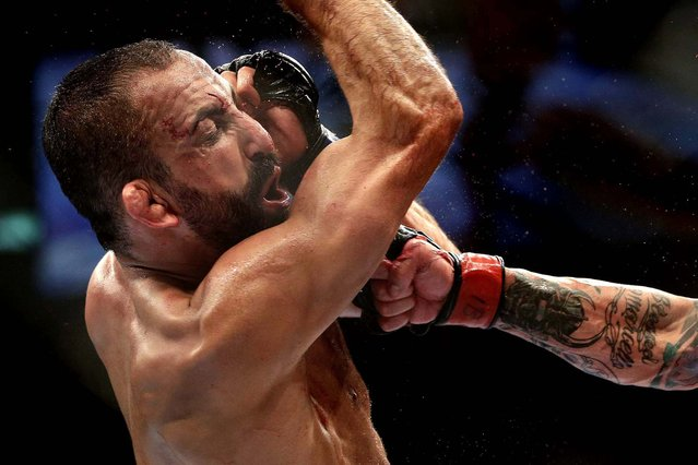 Reza Madadi, from Sweden, reacts to a punch from Cristiano Marcello of Brazil during their lightweight mixed martial arts bout. Marcello defeated Madadi at the Ultimate Fighting Championship (UFC) 153 in Rio de Janeiro, Brazil, October 13, 2012. (Photo by Felipe Dana/Associated Press)