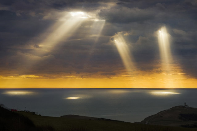 """This breathtaking natural light show illuminating waters off the British coast looks like something out of hit film """"Close Encounters of the Third Kind"""". Photographer Adrian Campfield was out having dinner at a restaurant at Beachy Head, East Sussex, when the rays suddenly appeared. The 59-year-old and his wife Louise rushed outside onto the 535ft high cliffs to watch the spectacle. (Photo by Adrian Campfield/Solent/Visual Press Agency)"""