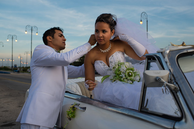 As the sun sets on the Malecon in Havana on Friday January 23, 2015, Nelson Boo Gonzalez, 26, left, helps his wife of only hours, Yunaisis Conconon Isaac, 25, with her necklace. (Photo by Sarah L. Voisin/The Washington Post)