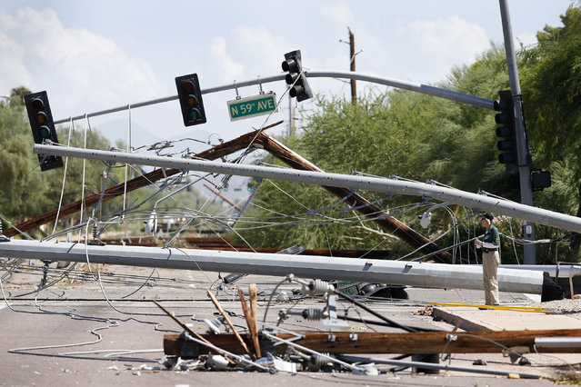 A security worker surveys the damage as she is surrounded by downed power lines strewn across a street Sunday, September 28, 2014, in Glendale, Ariz., the day after violent storms swept through the Phoenix metro area. The storm brought heavy rain and strong winds to the region Saturday – flooding roads, delaying flights and leaving thousands without power. (Photo by Ross D. Franklin/AP Photo)