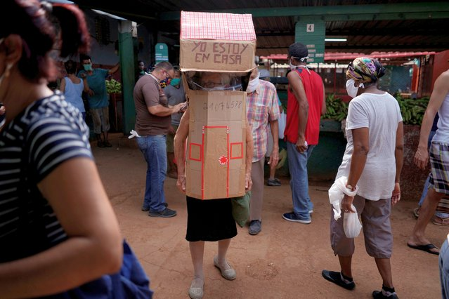 Retired nurse Feridia Rojas, 82, wears cardboard shaped into a house at a market to protect herself from the spread of the coronavirus disease (COVID-19) outbreak, in Havana, Cuba, June 11, 2020. (Photo by Alexandre Meneghini/Reuters)