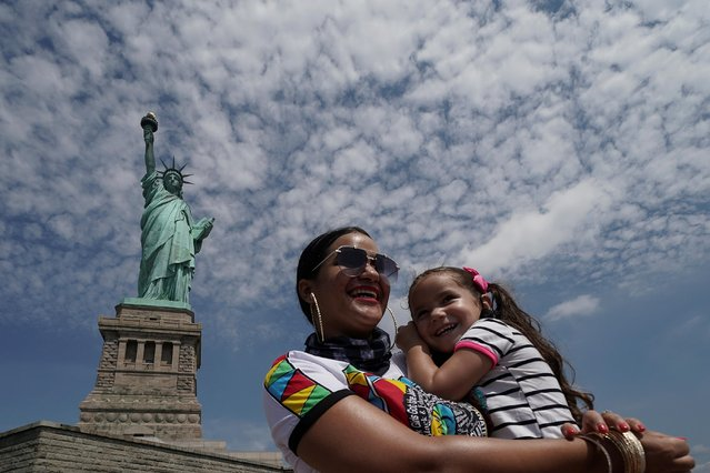 People pose for a photo at the Statue of Liberty as New York enters Phase 4 of reopening following the outbreak of the coronavirus disease (COVID-19) in New York City, New York, U.S., July 20, 2020. (Photo by Carlo Allegri/Reuters)