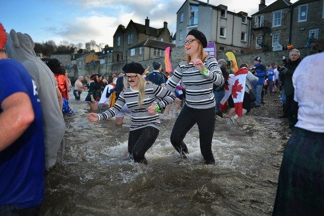 Over 1,000 New Year swimmers, many in costume, brave the freezing conditions in the River Forth in front of the Forth Rail Bridge during the annual Loony Dook Swim on January 1, 2013 in South Queensferry, Scotland. Thousands of people gathered last night to see in the New Year at Hogmanay celebrations in towns and cities across Scotland.  (Photo by Jeff J. Mitchell)