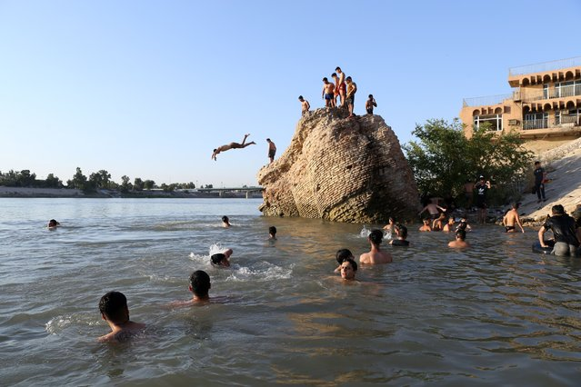 People cool themselves off by the cool waters of River Tigris as the temperature reaches at 50 Celcius degree and power cuts amid the novel coronavirus (COVID-19) pandemic at Azamiya also known as Al-Adhamiyah neighbourhood in Baghdad, Iraq on July 13, 2020. (Photo by Murtadha Al-Sudani/Anadolu Agency via Getty Images)