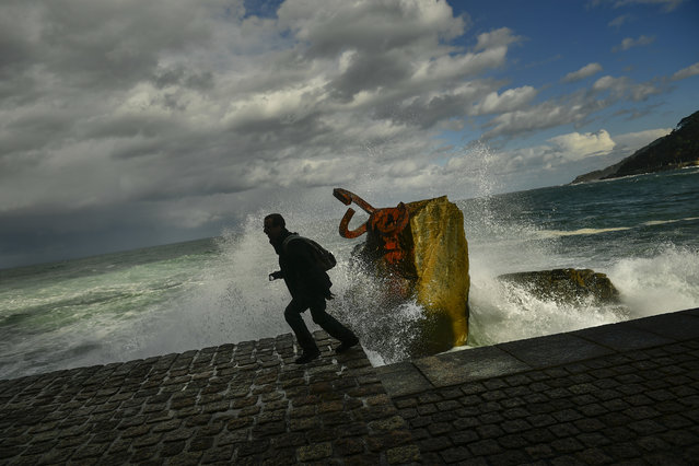 A man runs as a giant wave crashes against the sea defences during a high tide in San Sebastian, northern Spain, Monday, December11, 2017. Spain and Portugal have issued warnings of high winds and heavy rain as a storm reaches the Iberian Peninsula from the Atlantic. (Photo by Alvaro Barrientos/AP Photo)