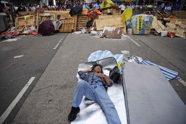 A man sleeps in front of a barricade built by pro-democracy protesters at the part of Mongkok shopping district their are occupying in Hong Kong November 2, 2014. (Photo by Damir Sagolj/Reuters)