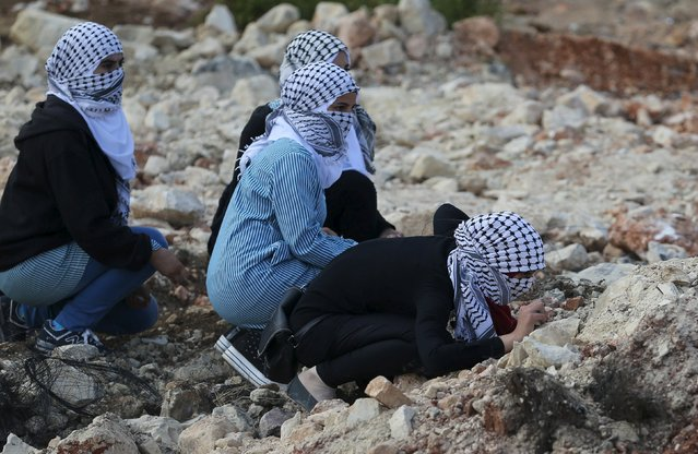Palestinian girls take cover during clashes with Israeli troops near the Jewish settlement of Bet El, near the West Bank city of Ramallah October 8, 2015.  Four people, including an Israeli soldier, were stabbed and wounded near a military headquarters in Tel Aviv on Thursday, police and ambulance sources said, as a rash of such Palestinian attacks spread to Israel's commercial capital. (Photo by Mohamad Torokman/Reuters)