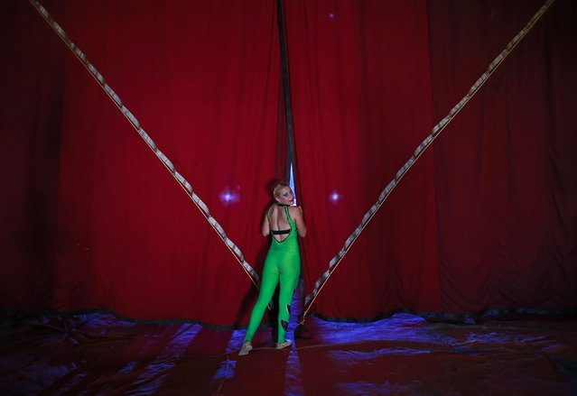 A female member of an acrobatic team looks from behind the curtains as she waits backstage before the start of her performance at the Rambo Circus in Mumbai November 6, 2014. The Rambo circus travels all over the country throughout the year. It has a seating capacity of 2,000 people and tickets are priced from 350 rupees ($5.60). (Photo by Danish Siddiqui/Reuters)