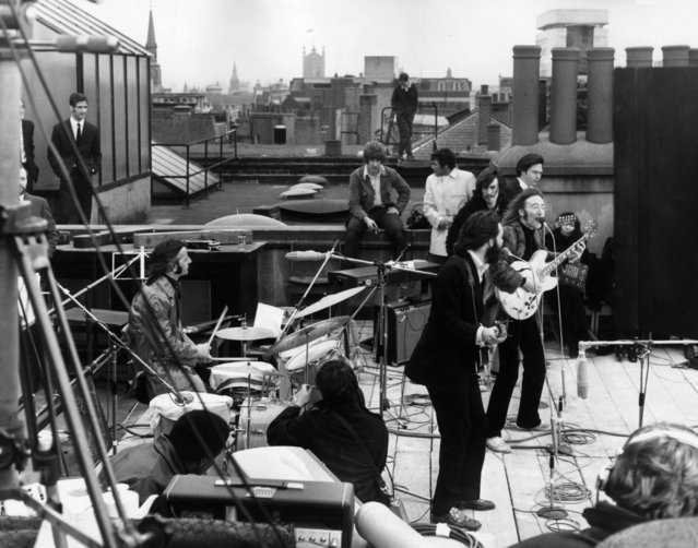 "British rock group the Beatles performing their last live public concert on the rooftop of the Apple Organization building for director Michael Lindsey-Hogg's film documentary, ""Let It Be"", on Savile Row, London, England, 30th January 1969. Drummer Ringo Starr sits behind his kit. Singer/songwriters Paul McCartney and John Lennon perform at their microphones, and guitarist George Harrison (1943 - 2001) stands behind them. Lennon's wife Yoko Ono sits at right. (Photo by Express/Express/Getty Images)"