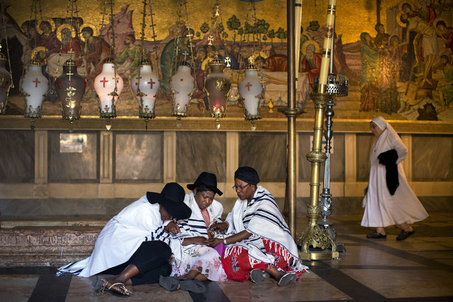 Three Christian pilgrims from London covered in Jewish prayer shawls pray in the Church of the Holy Sepulchre in Jerusalem's old city, Sunday, September 18, 2016. (Photo by Oded Balilty/AP Photo)