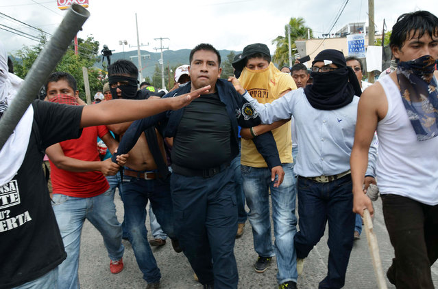 Masked teachers detain a police officer during clashes in Chilpancingo, the capital of Guerrero state, Mexico, Tuesday, November 11, 2014. Supporters of 43 missing college rural students, refusing to believe they are dead, have kept up the protests that have blocked major highways and set government buildings ablaze in recent weeks. The students disappeared at the hands of a city police force on Sept. 26 in the town of Iguala. (Photo by Alejandrino Gonzalez/AP Photo)