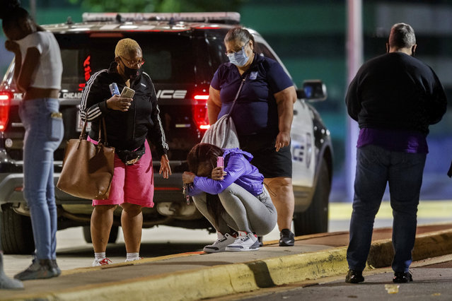 A woman kneels on the ground outside the University of Chicago Medicine's Comer Children's Hospital where a 8-year-old girl was taken after being killed in a shooting that wounded three others near the intersection of 47th street and Union Avenue during the Labor Day weekend, Monday Sepember 7, 2020 in Chicago. (Photo by Armando L. Sanchez/Chicago Tribune via AP Photo)
