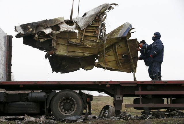 Local workers transport wreckage of the Malaysia Airlines Boeing 777 plane (flight MH17) at the site of the plane crash near the village of Hrabove (Grabovo) in Donetsk region, eastern Ukraine November 16, 2014. (Photo by Maxim Zmeyev/Reuters)