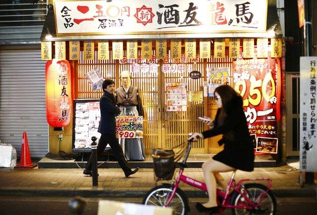 A man walks past a restaurant in the Dotonbori amusement district of Osaka, western Japan November 19, 2014. (Photo by Thomas Peter/Reuters)