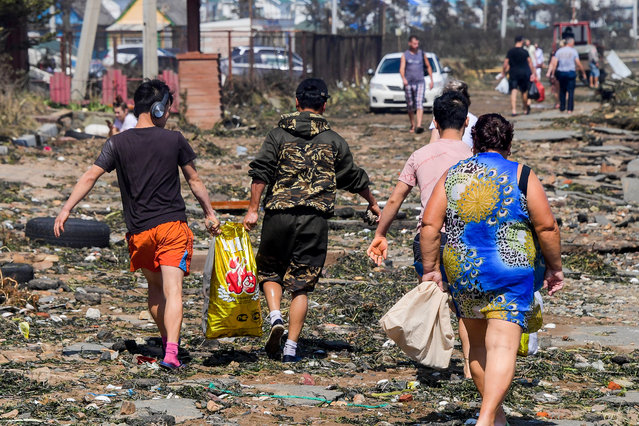 Local people collect shellfish and items washed onto Shamora Beach by high waves caused by Typhoon Maysak on the shore of Lazurnaya Bay in the city of Vladivostok, on Russia's Pacific coast on September 4, 2020. (Photo by Yuri Smityuk/TASS via Getty Images)