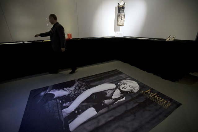 David Strasberg, son of American acting coach Lee Strasberg who was a friend and mentor to actress Marilyn Monroe, walks past an oversized photograph of Monroe at an exhibition of her personal effects in Beijing, Tuesday, September 27, 2016. (Photo by Mark Schiefelbein/AP Photo)