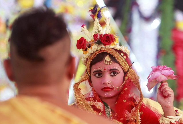 A Hindu (L) priest performs traditional worship of Nilanjana Chakraborty, a five-year old girl dressed as a Kumari, during the religious festival of Durga Puja in Agartala, India, October 21, 2015. (Photo by Jayanta Dey/Reuters)