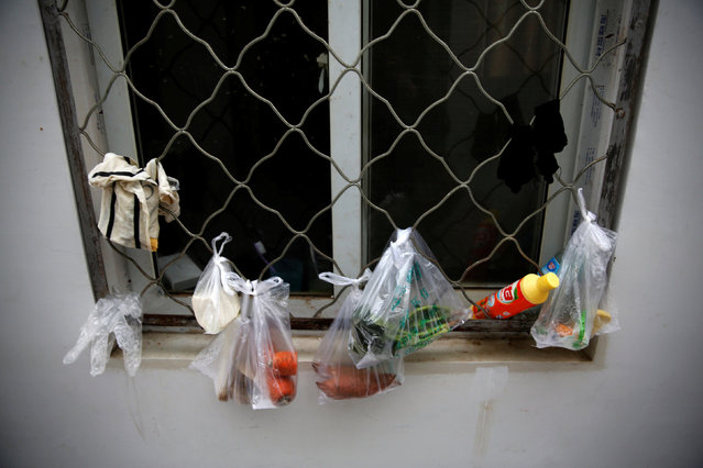 Groceries in plastic bags hang by the window at the accommodation where some patients and family members stay while seeking medical treatment in Beijing, China, October 23, 2015. (Photo by Kim Kyung-Hoon/Reuters)