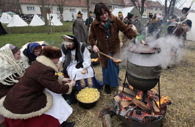 History enthusiasts cook before the re-enactment of Napoleon's famous battle of Austerlitz near the southern Moravian town of Slavkov u Brna November 29, 2014. (Photo by David W. Cerny/Reuters)