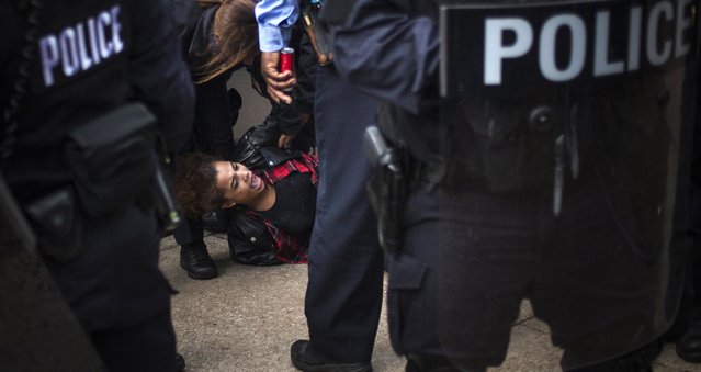 Police in riot gear arrest a protester, who was demanding justice for Michael Brown, for disrupting traffic some blocks away from the Edward Jones Dome, the site of an NFL football game between the St. Louis Rams and the Oakland Raiders, in downtown St. Louis, Missouri November 30, 2014. (Photo by Adrees Latif/Reuters)
