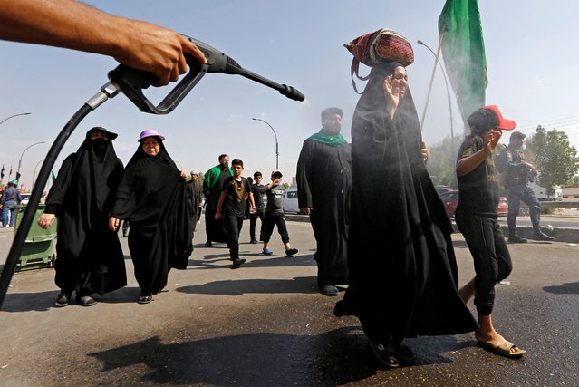 Iraqi Shi'ite Muslim pilgrims are sprayed with water to cool them as they make their way to the holy city of Kerbala, ahead of the holy Shi'ite ritual of Arbaeen, amid the outbreak of the coronavirus disease (COVID-19), in Baghdad, Iraq on October 5, 2020. (Photo by Thaier Al-Sudani/Reuters)