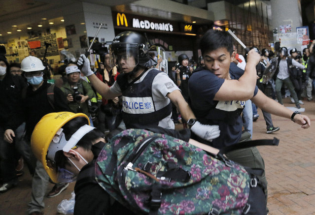 Police officers beat up protesters as they try to disperse them outside government headquarters in Hong Kong Monday, December 1, 2014. Pro-democracy protesters clashed with police as they tried to surround Hong Kong government headquarters late Sunday, stepping up their movement for genuine democratic reforms after camping out on the city's streets for more than two months. (Photo by Vincent Yu/AP Photo)