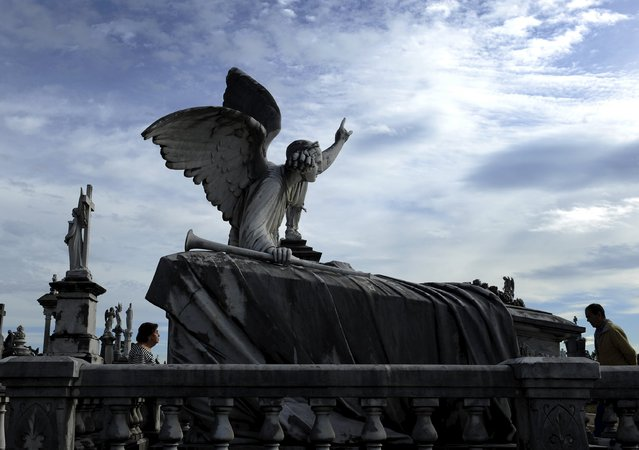 People walk next to of the pantheon of the Marquesa de San Juan de Nieva, chosen as the best tomb sculpture of Spain in a Spanish magazine this week, in the municipal cemetery of La Carriona in Aviles, northern Spain, October 29, 2015. Catholics will mark All Saints' Day on Sunday by visiting cemeteries and graves of deceased relatives and friends. (Photo by Eloy Alonso/Reuters)