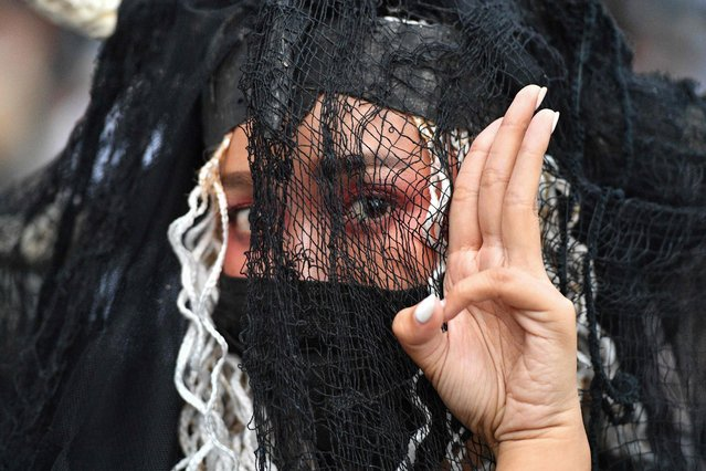 A woman gives the three-finger salute associated with pro-democracy protesters during an open-air art exhibition in Silom in Bangkok on October 29, 2020. (Photo by Mladen Antonov/AFP Photo)