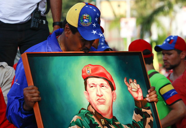 Venezuela's acting President and presidential candidate Nicolas Maduro kisses a painting of late Venezuelan president Hugo Chavez during a campaign rally in the state of Vargas April 9, 2013. Venezuelans will hold presidential elections on April 14. Maduro promised on Tuesday to hike Venezuela's minimum wage by about 40 percent if he is elected in a weekend vote to replace late socialist leader Chavez. (Photo by Carlos Garcia Rawlins/Reuters)