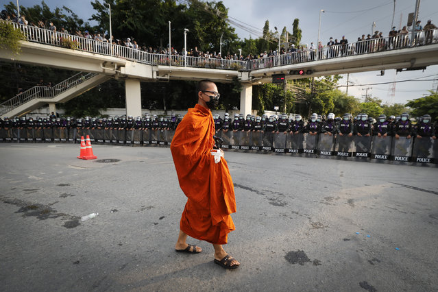 A monk walk pass police blocking protesters in a main intersection as he returns to his temple near the Parliament in Bangkok, Tuesday, November 17, 2020. (Photo by Sakchai Lalit/AP Photo)