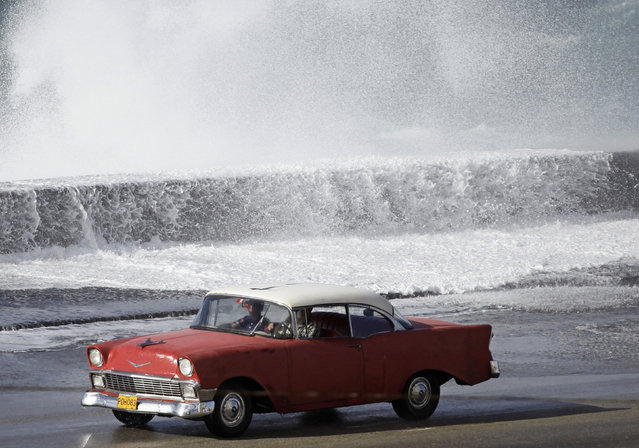 A 1956 Chevrolet automobile drives along Havana's seafront boulevard as waves break, March 13, 2010. (Photo by Desmond Boylan/Reuters)