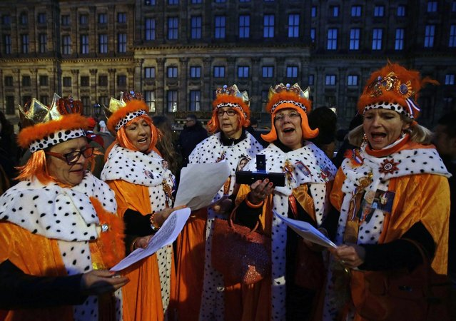 People wait outside the Royal Palace in Amsterdam April 30, 2013. The Netherlands is preparing for Queen's Day on Tuesday, which will also mark the abdication of Queen Beatrix and the investiture of her eldest son Willem-Alexander. (Photo by Kevin Coombs/Reuters)
