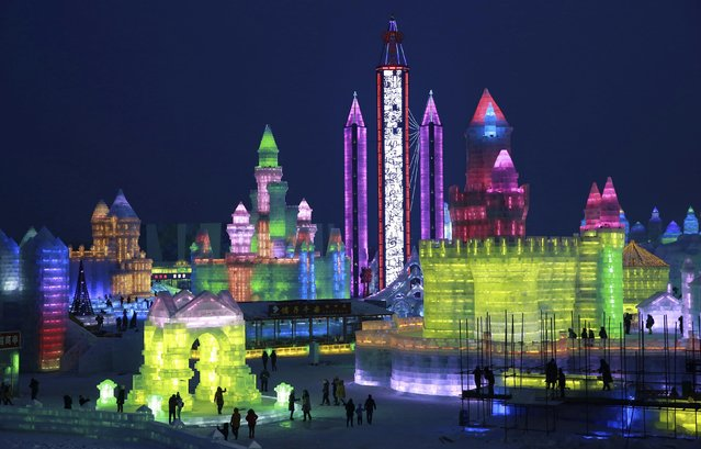 People visit newly-built ice sculptures illuminated by coloured lights during a trial operation of the 16th Harbin Ice and Snow World in Harbin, Heilongjiang province, December 22, 2014. The annual Harbin Ice and Snow World will be officially opened on January 5, 2015. (Photo by Reuters/Stringer)