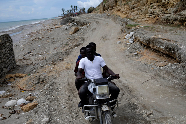 Three men ride a motorbike on the road after Hurricane Matthew in Chardonnieres, Haiti, October 17, 2016. (Photo by Andres Martinez Casares/Reuters)