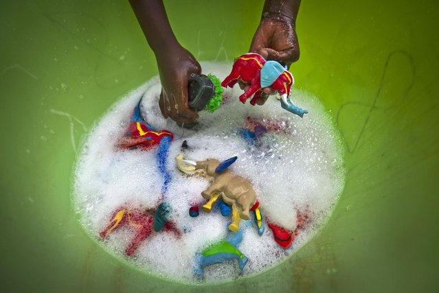 In this photo taken Monday, April 29, 2013, a female worker washes some finished toy animals made from pieces of discarded flip-flops, in a bucket at the Ocean Sole flip-flop recycling company in Nairobi, Kenya. The company is cleaning the East African country's beaches of used, washed-up flip-flops and the dirty pieces of rubber that were once cruising the Indian Ocean's currents are now being turned into colorful handmade giraffes, elephants and other toy animals. (Photo by Ben Curtis/AP Photo)