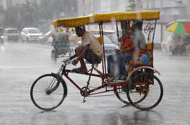 A man transports passengers on an improvised motorized rickshaw during heavy rains in Agartala, India, April 20, 2018. (Photo by Jayanta Dey/Reuters)