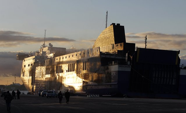 The Norman Atlantic multi-deck car-and-truck ferry is seen at the dock of Brindisi harbour, after a fire broke out on it off the coast of Greece, January 2, 2015. Tug boats hauled the burnt-out hulk of the ferry to the southern Italian port on Friday, opening the way for an investigation into the cause of the blaze that killed at least 11 people. The ferry caught fire off Greece's Adriatic Coast on December 28, 2014 whilst on a voyage to Italy. (Photo by Ciro De Luca/Reuters)