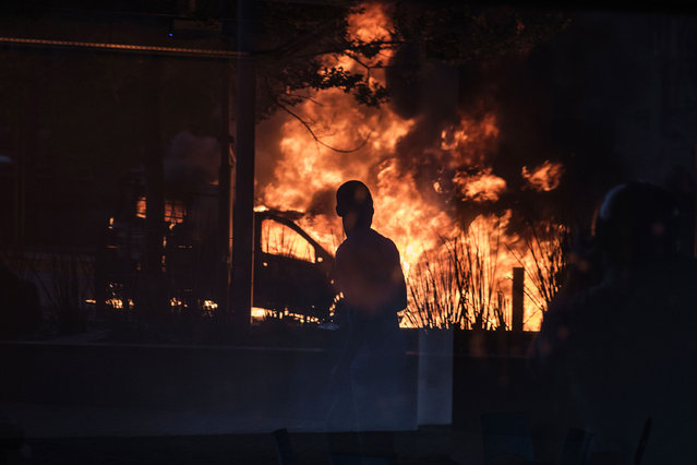 A passing bystander is reflected in a shop window as a South African police van is set on fire on October 25, 2016 in Johannesburg, during a university students' protest against tuition fees, racism and inequality. Weeks of demonstrations at South African universities have targeted high student tuition fees – but protestors say they are also about inequality in a society still plagued by the legacy of apartheid. (Photo by Gianluigi Guercia/AFP Photo)