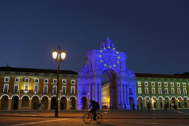 The arch at Lisbon's Comercio square is illuminated to mark the start of the Portuguese Presidency of the Council of the European Union, Friday, January 1, 2021. Portugal will hold the rotating presidency during the first semester of 2021. (Photo by Armando Franca/AP Photo)