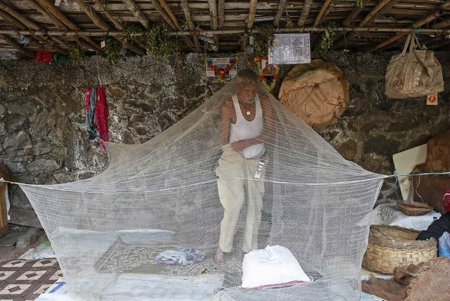 A vendor gets dressed under a mosquito net at his roadside shop in Mumbai January 5, 2015. (Photo by Danish Siddiqui/Reuters)