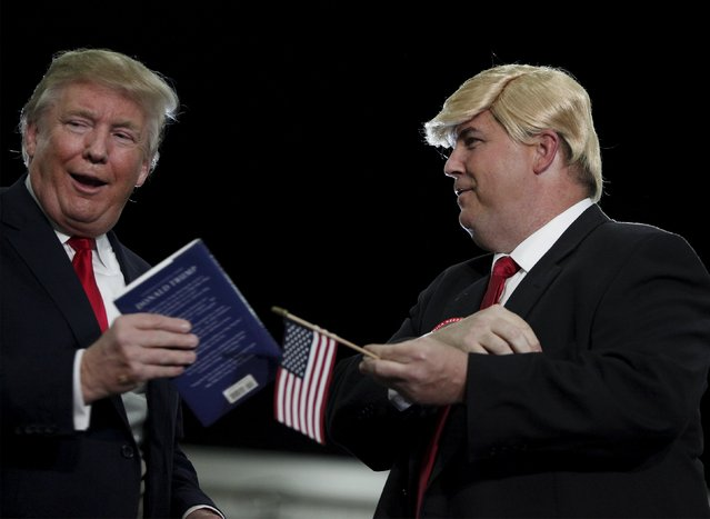 U.S. Republican presidential candidate Donald Trump (L) brings a look-alike supporter Terry Silliman of Goose Creek, South Carolina on stage during a rally at the Myrtle Beach Convention Center in Myrtle Beach, South Carolina, November 24, 2015. (Photo by Randall Hill/Reuters)