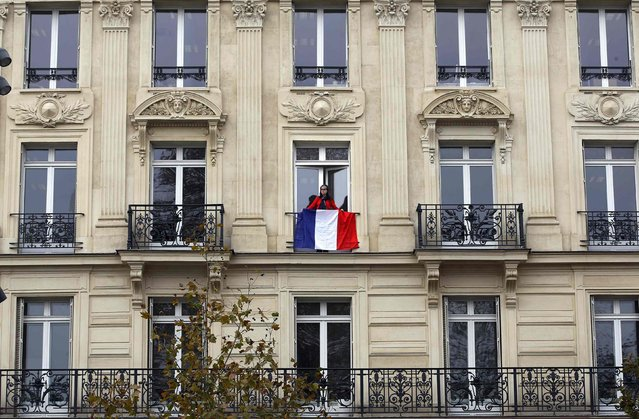 A woman stands on a balcony behind a French flag at an apartment building in the Place de la Republique in Paris, France, November 27, 2015 as the French President called on all French citizens to hang the tricolour national flag from their windows on Friday to pay tribute to the victims of the Paris attacks during a national day of homage. (Photo by Eric Gaillard/Reuters)