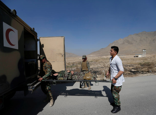 Afghan National Army (ANA) soldiers carry their colleague, with a simulated injury, into an ambulance during a training exercise at the Kabul Military Training Centre (KMTC) in Kabul, Afghanistan October 26, 2016. (Photo by Mohammad Ismail/Reuters)