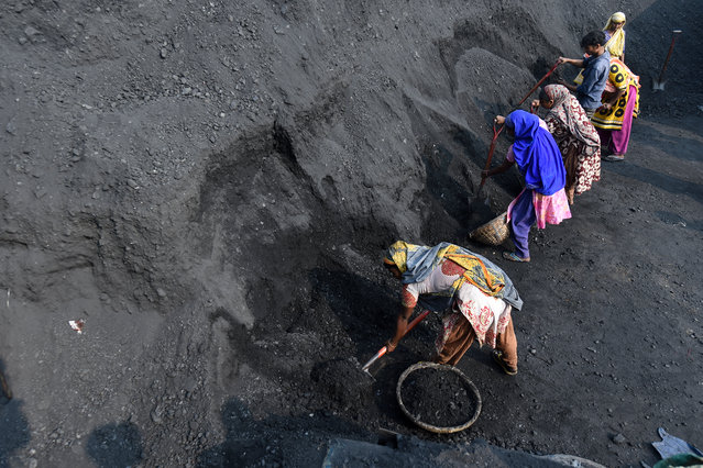 Workers load up coal into baskets in Dhaka on December 28, 2020. (Photo by Munir Uz Zaman/AFP Photo)