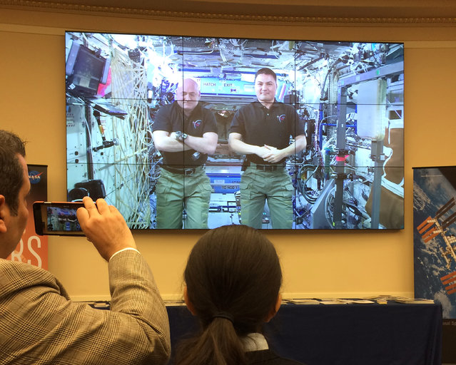 People watch on a video screen on Capitol Hill in Washington, Wednesday, December 2, 2015, as astronauts Scott Kelly, left, and Kjell Lindgren testify from the International Space Station before the House Science, Space and Technology Committee. Testifying from space, Kelly said it has been helpful to be able to grow things in the International Space Station, where he is stationed for a full year. (Photo by Mary Clare Jalonick/AP Photo)